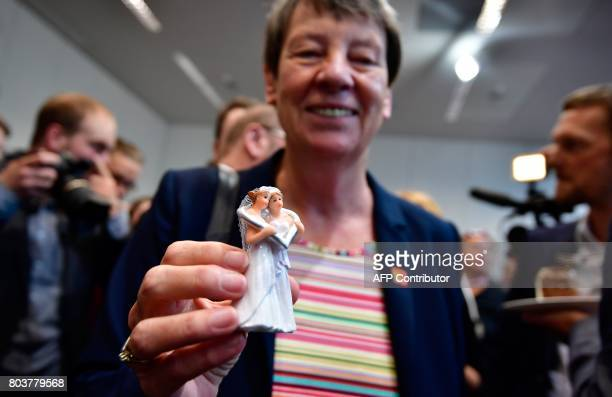 German Environment Minister Barbara Hendricks holds a figurine of two women in wedding dresses as she poses at the offices of her social democratic...