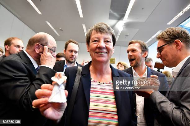 German Environment Minister Barbara Hendricks of the social democratic SPD party holds a figurine of two women in wedding dresses as SPD leader and...