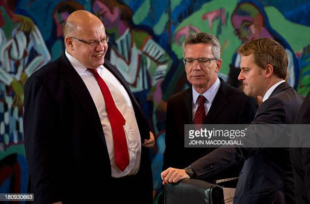 German Environment Minister Peter Altmaier German Defence Minister Thomas de Maiziere and German Health Minister Daniel Bahr chat prior to a weekly...