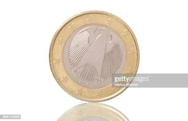 German euro coin, on slope, symbolic image for euro crisis