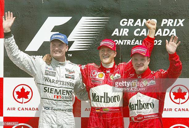 German F1 driver Michael Schumacher of Team Ferrari celebrates with second place finisher David Coulthard of Team McLaren and third place finisher...