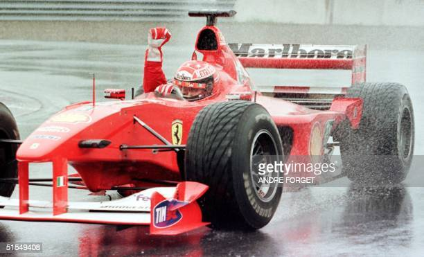 German F1 driver Michael Schumacher of Team Ferrari raises his arms as he takes his victory lap after winning the 2000 Canadian Grand Prix 18 June at...