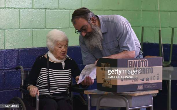 German Fainzildr assists his elederly mother Sara to cast her vote at a polling station set up at Carlos Sanabria elementary school in San Jose...