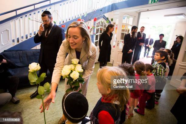 German Family Minister Kristina Schroeder gets a white rose as she visits the Gan Israel Jewish kindergarten on May 16 2012 in Berlin Germany Berlin...