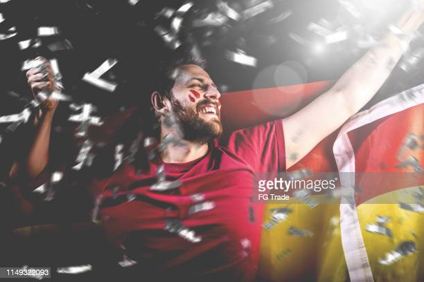 german fan celebrating with the national flag - football league stock pictures, royalty-free photos & images