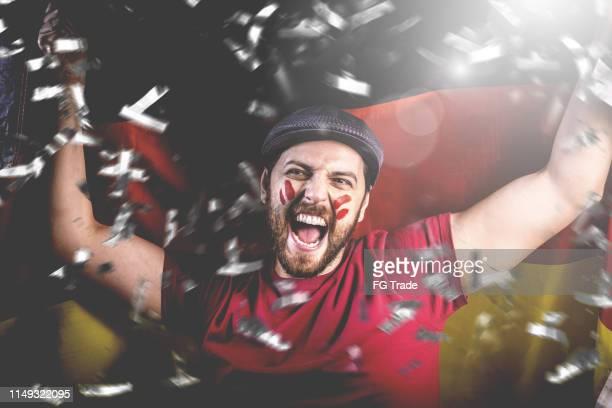 deutscher fan feiert mit der nationalflagge - deutsche fußball liga stock-fotos und bilder