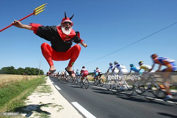 German fan Didi Senft known as El Diablo jumps as the racers ride past on July 9 during in the 232 km fifth and longest stage of the 2008 Tour de...