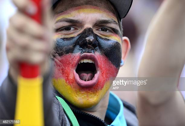 A German fan has his face painted with the German national colours as he waits in front of a stage installed for a victory parade of Germany's...