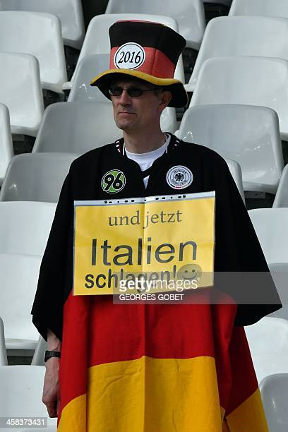 """German fan holds a placard reading """"And now let's beat Italy"""" before the Euro 2016 quarter-final football match between Germany and Italy at the..."""
