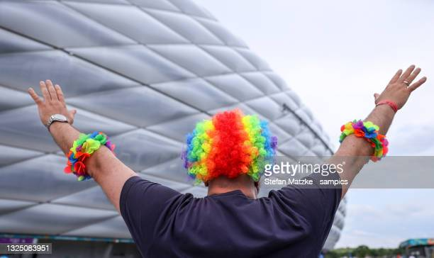German fan poses in a rainbow flag coloured wig in front of the Munich Stadium before the UEFA Euro 2020 Championship Group F match between Germany...