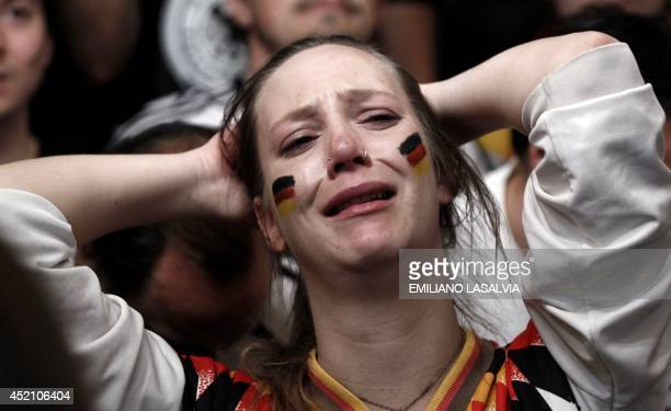 A German fan watches the FIFA World Cup Brazil 2014 final match between Germany and Argentina at a pizzeria in Buenos Aires on July 13 2014 AFP PHOTO...