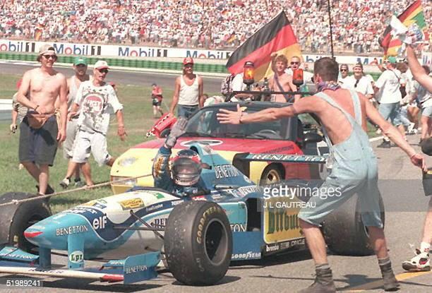 German Fans celebrate around national idol Michael Schumacher driving his BenettonRenault on the Hockenheim racetrack 30 July after he won the German...