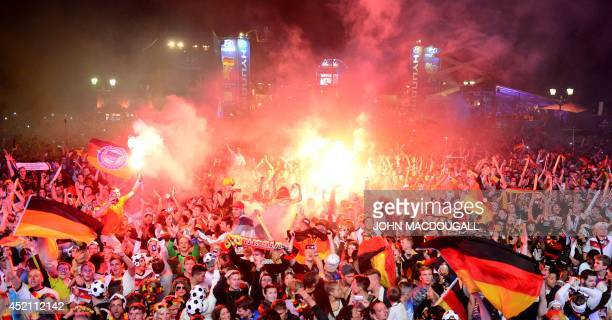 German fans celebrate at an outdoor screening near the Brandenburg Gate in Berlin on July 13 as Germany won the FIFA World Cup 2014 final football...