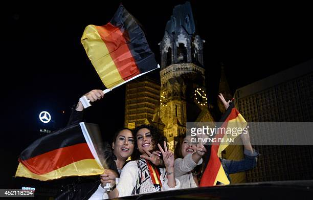 German fans celebrate with national flags on a car near the Zoo train station on early July 14 2014 in Berlin after Germany won the FIFA World Cup...