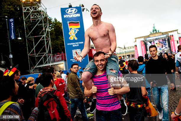 German fans celebrating at the Hyundai Fan Park public viewing area named 'Fan Mile' in front of the Brandenburg Gate in Tiergarten park after...