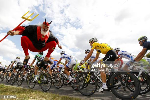 German fans El Diablo jumps as yellow jersey of overall leader Norway's Thor Hushovd rides in the pack during the 218 km and seventh stage of the...