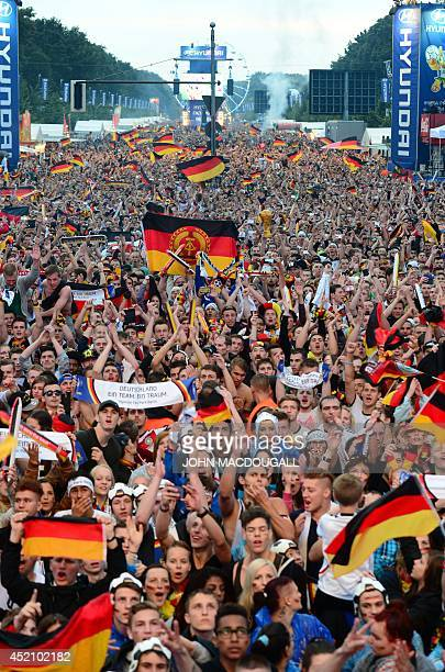 German fans hold the eastGerman flag as they watch the opening ceremony of the FIFA World Cup 2014 final football match Germany vs Argentina played...