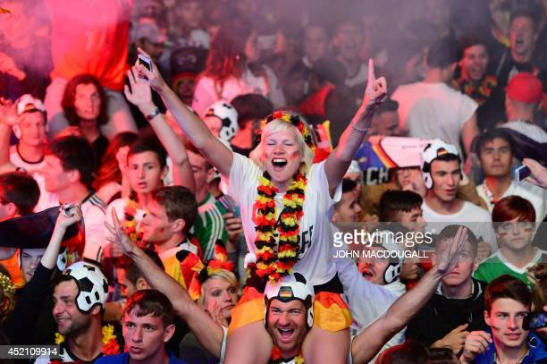 German fans react as Germany score during the FIFA World Cup 2014 final football match Germany vs Argentina played in Brazil during an outdoor...