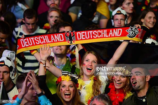 German fans react as they watch the FIFA World Cup 2014 final football match Germany vs Argentina played in Brazil during an outdoor screening near...