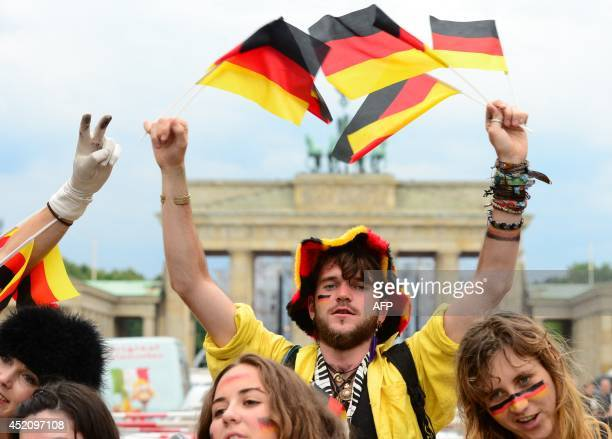 German fans wave with national flags in front of the Brandenburg Gate in Berlin on July 13 2014 where the FIFA World Cup 2014 final football match...