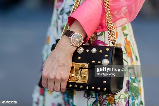 German fashion blogger and model Alexandra Lapp is wearing a black Padlock shoulder bag by Gucci a pink blouse by Gucci pleated Flora snake silk...