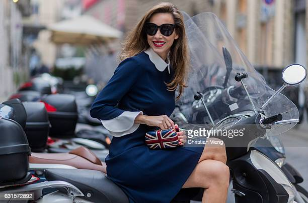 German fashion blogger and model Alexandra Lapp sitting on an Italian vespa is wearing navy blue kneelength shirt dress in flared cut with removable...