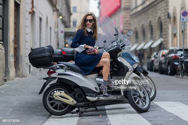 German fashion blogger and model Alexandra Lapp sitting on an Italian vespa is wearing navy blue knee-length shirt dress in flared cut with removable...