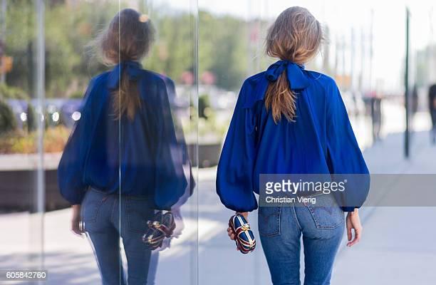 German Fashion Blogger and Model Alexandra Lapp wearing a blue blouse from Steffen Schraut Levis jeans Alexander Mc Queen clutch on September 14 2016...