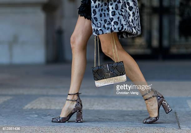German fashion blogger and model Alexandra Lapp wearing a Patrizia Pepe coat with leo print black dress Patrizia Pepe bag and heels outside...