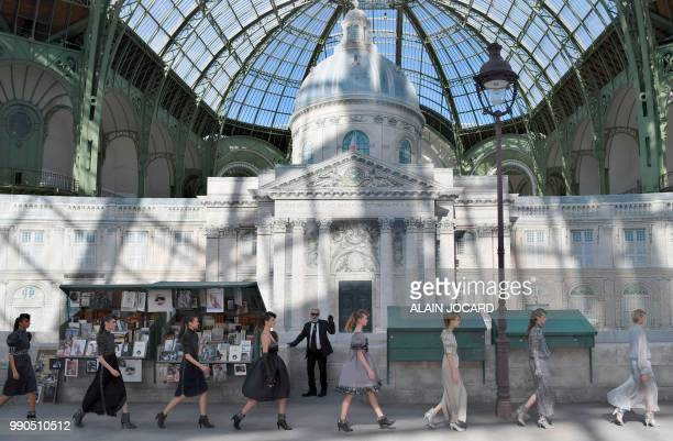 TOPSHOT German fashion designer Karl Lagerfeld acknowledges the audience at the end of the Chanel 20182019 Fall/Winter Haute Couture collection...