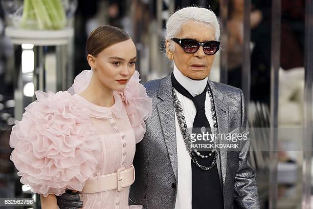 German fashion designer Karl Lagerfeld acknowledges the audience next to French and US actress and model LilyRose Melody Depp at the end of the...