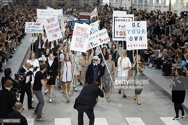 German fashion designer Karl Lagerfeld acknowledges the public along with models faking a demonstation as they present creations for Chanel during...