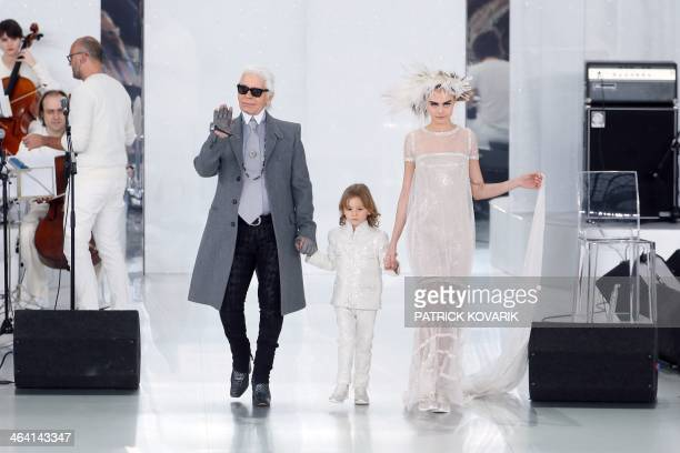 German fashion designer Karl Lagerfeld acknowledges the public along with his godson Hudson Kroenig and British model Cara Delevingne during the...
