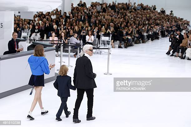 German fashion designer Karl Lagerfeld acknowledges the public at the end along with British model Cara Delevingne and his godson Hudson Kroenig...