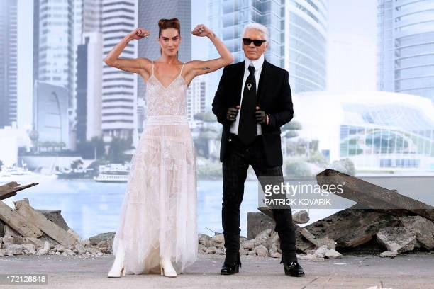 German fashion designer Karl Lagerfeld acknowledges the public with US model Erin Wasson at the end of the Chanel Haute Couture FallWinter 2013/2014...