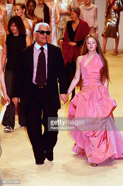 German fashion designer Karl Lagerfeld and a fashion model wearing a women's haute couture pink halter and skirt designed by Lagerfeld for French...