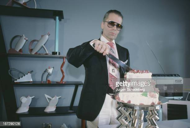 German fashion designer Karl Lagerfeld cutting a cake 1984 Behind him are a set of teapots from his Memphis collection