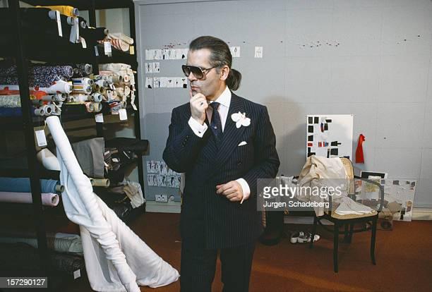 German fashion designer Karl Lagerfeld examines some rolls of fabric, 1984.