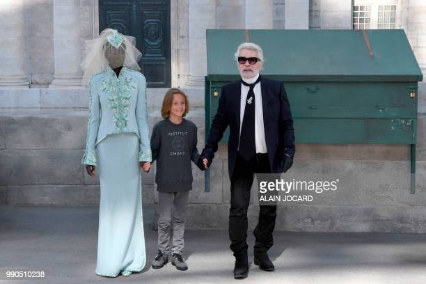German fashion designer Karl Lagerfeld flanked by his godson Hudson Kroenig and South SudaneseAustralian model Adut Akech acknowledges the audience...