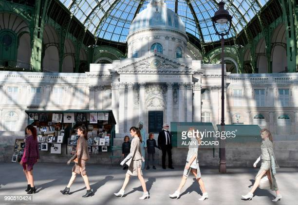 German fashion designer Karl Lagerfeld flanked by his godson Hudson Kroenig acknowledges the audience at the end of the Chanel 20182019 Fall/Winter...
