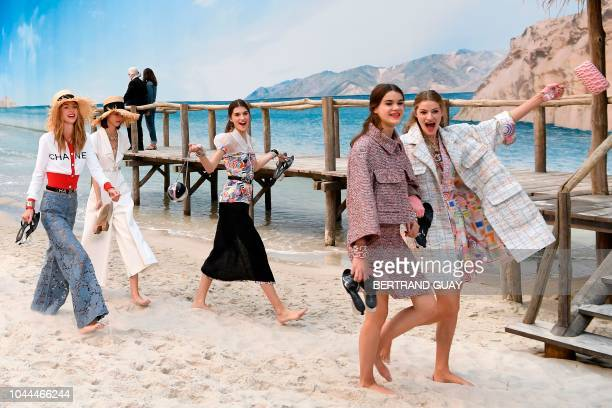 German fashion designer Karl Lagerfeld in the background acknowledges the audience as models present creations by Chanel at the end of the Chanel...