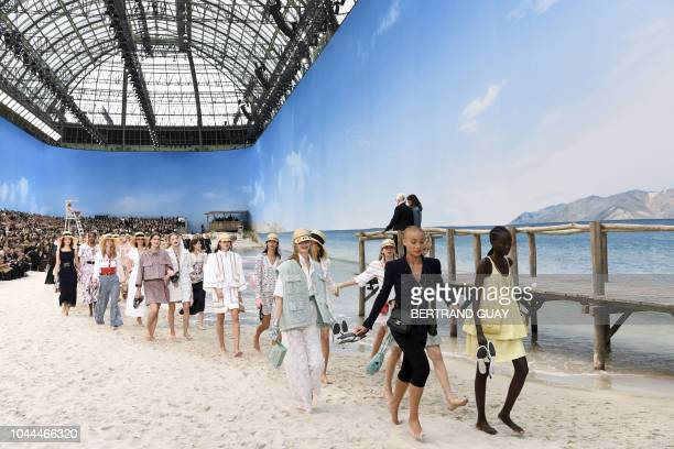 TOPSHOT German fashion designer Karl Lagerfeld in the background acknowledges the audience as models present creations by Chanel at the end of the...