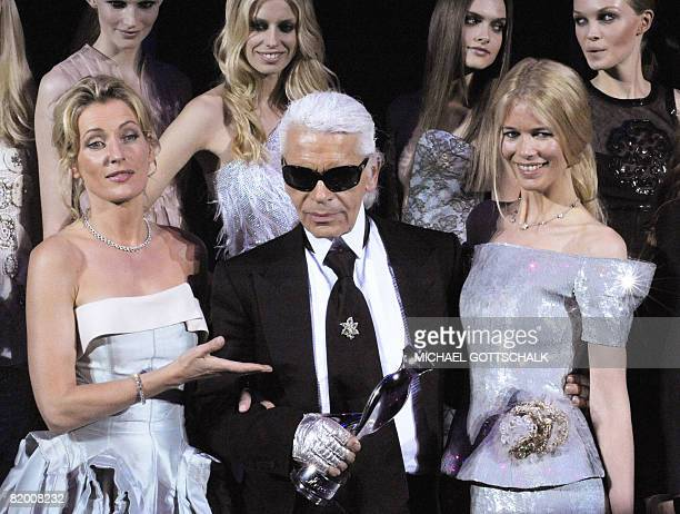 German fashion designer Karl Lagerfeld is flanked by German top model Claudia Schiffer and German actress Maria Furtwaengler after being given the...