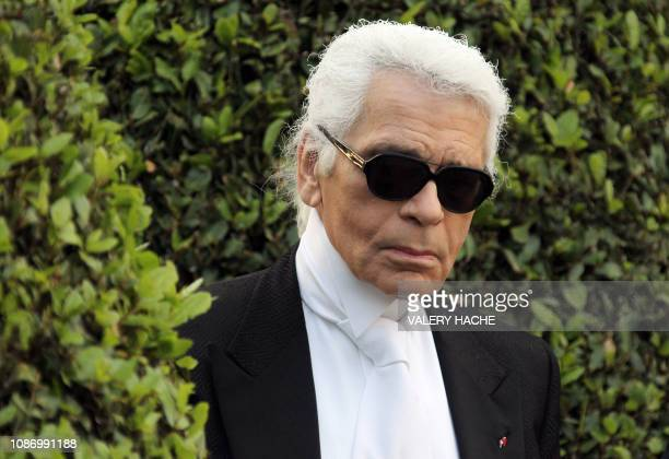 German fashion designer Karl Lagerfeld looks at models presenting some of his creations during the Croisiere collection show in Antibes southeastern...
