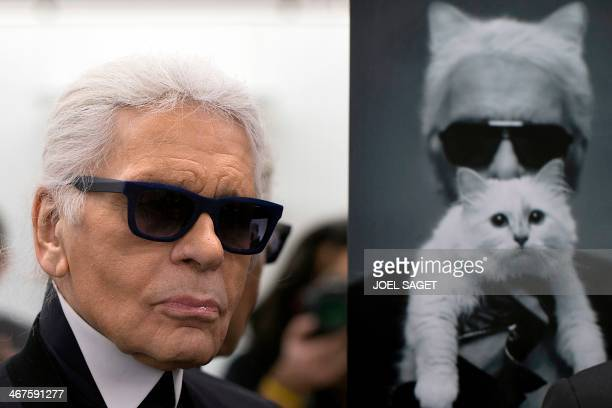 German fashion designer Karl Lagerfeld poses next to a photo of himself and his cat Choupette during a visit to the workshops that work for Chanel in...