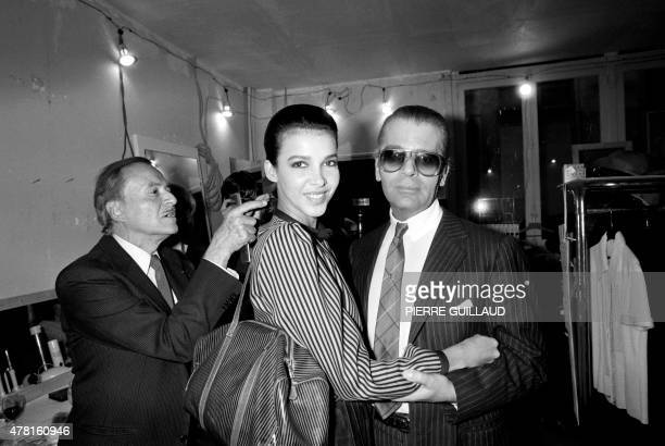 German fashion designer Karl Lagerfeld poses on January 24 1983 with a model as French hairdresser Alexandre de Paris prepares her backstage ahead of...