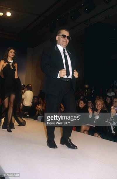 German fashion designer Karl Lagerfeld receives the audience's applause as he walks down the catwalk followed by fashion model Helena Christensen...