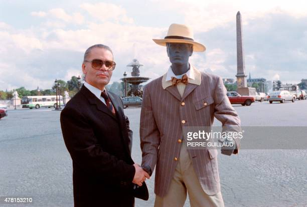 German fashion designer Karl Lagerfeld shakes hands with a wooden mannequin on September 5 1988 at Place de la Concorde in Paris as he presents his...