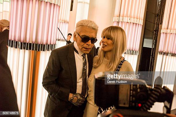 German fashion designer Karl Lagerfeld talks with model and actress Claudia Schiffer during a fashion show at his Chanel headquarters Paris France...