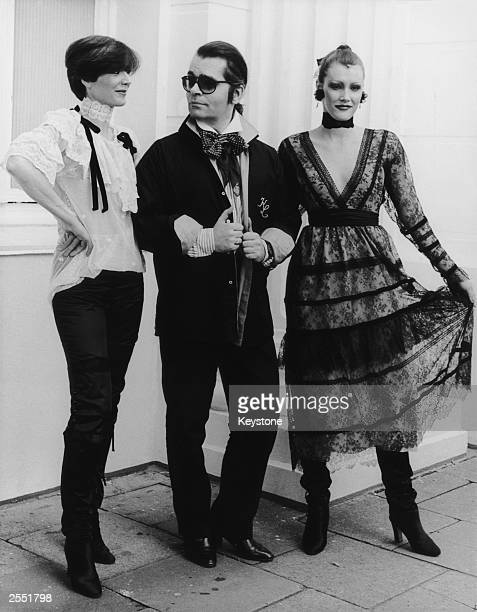 German fashion designer Karl Lagerfeld with two models, circa 1984.